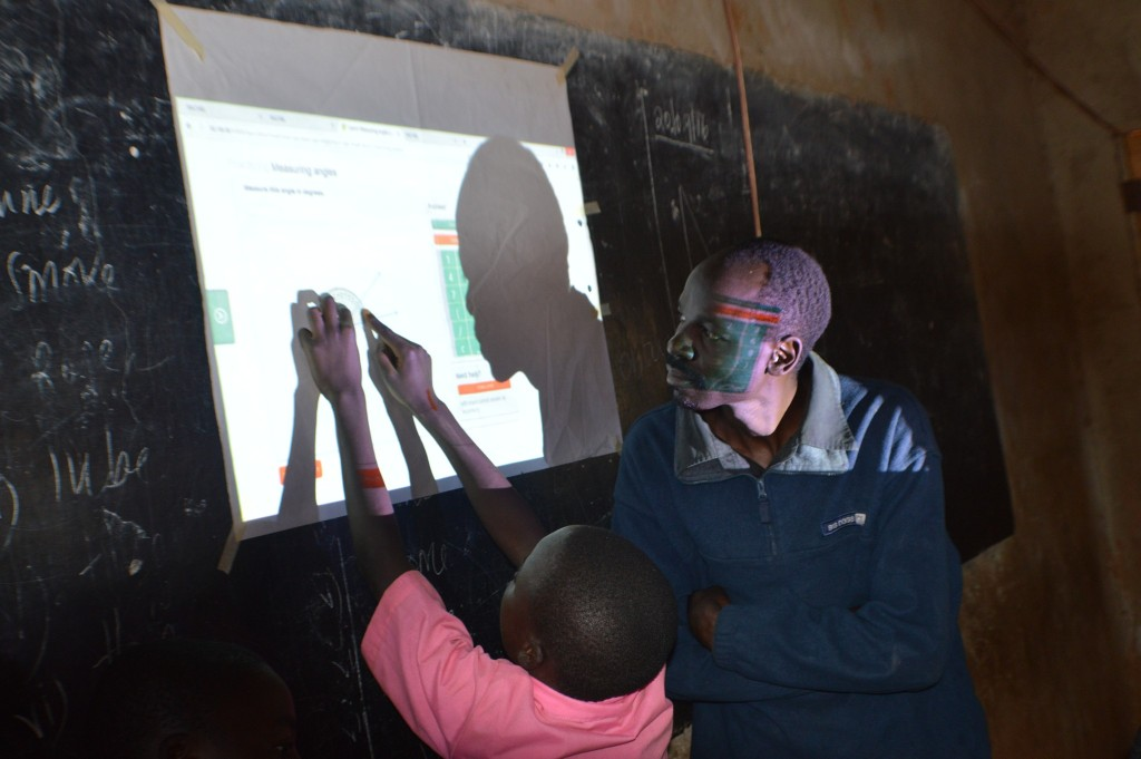 Mr Alex Anyova, a class five maths teacher looks on as one of his pupils measures angles using educational materials projected from RACHEl.